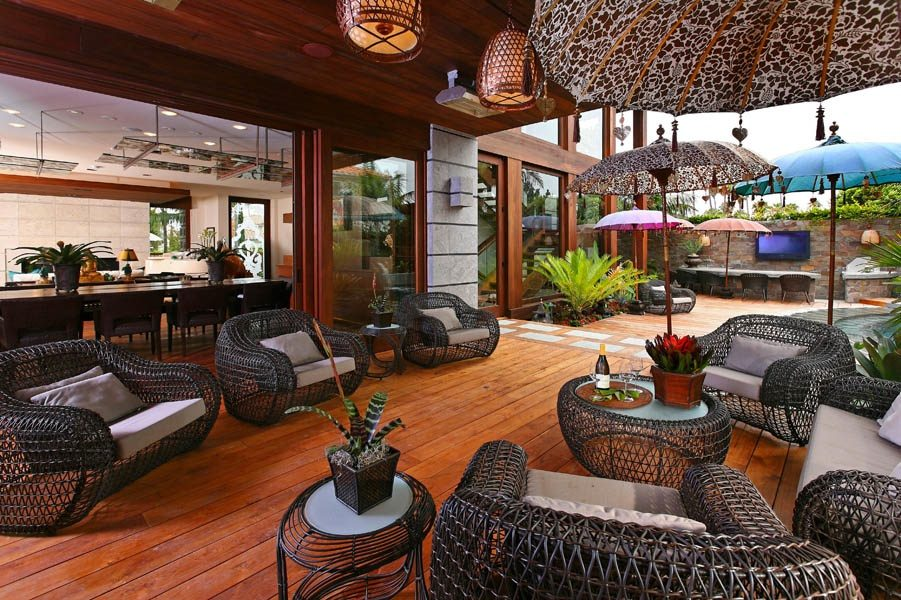 Dark wicker furniture, warm wooden floors, and large lacey umbrellas sit among sago palms, contemporary stone work, and lantern like pendant lights in this outdoor patio.